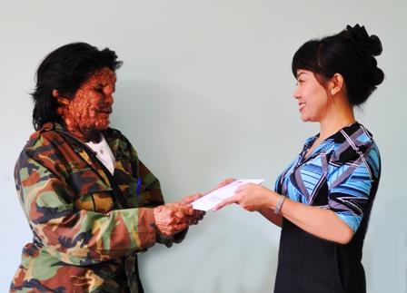Tác giả trao tiền độc giả giúp ông Tê. Ảnh ( Vạn Tiếp )