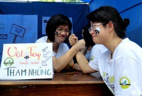 """Hai thành viên của CLB Đen và Trắng tham dự thi vật tay với khẩu hiệu """"Vật tay thổi bay tham nhũng"""" tại một hoạt động của giới trẻ tại Hà Nội vào tháng 11/2012 nhằm thúc đẩy môi trường giáo dục công bằng."""