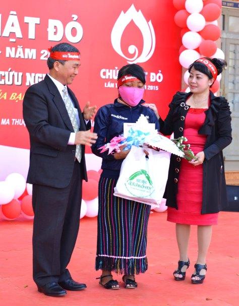 Đồng chí Trương Văn Tỵ Vụ trưởng Vụ Dân tộc & Tôn giáo Ban Chỉ đạo Tây Nguyên cùng nhà báo Hoàng Thiên Nga trao quà của BTC chương trình hỗ trợ điều trị cho bệnh nhân K vòm mặt H'Loai Niê