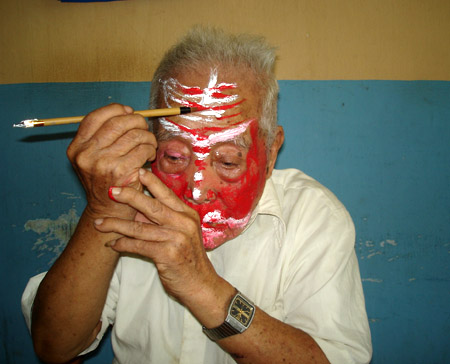 Cố nghệ nhân La Cháu, nghệ nhân cuối cùng dưới triều Nguyễn, đang tự kẻ mặt nạ trước khi biểu diễn