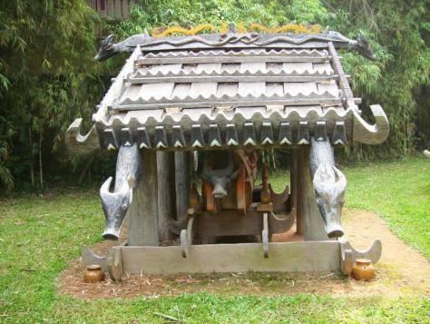 Nhà mồ pinh blâng của người Cơ Tu ở Quảng Nam được phục dựng tại Bảo tàng Dân tộc học. Hình tượng con trâu luôn xuất hiện ở những công trình kiến trúc như: gươl, quan tài, nhất là nhà mồ, rất rõ nét, sinh động. Trong ảnh là phác thảo hình đầu trâu để tạc tượng ở hai đầu quan tài và ở một phía đầu hồi nóc của nhà mồ.