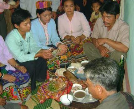 Người Ơ Đu đang xem chân gà ngày tết Chăm Phtrong tại nhà cộng đồng (ảnh CT).