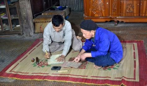 Ông Hoàng Văn Phúc, dân tộc Tày ở thôn Nà Coóc, xã Bộc Bố, huyện Pác Nặm đang truyền dạy chữ Nôm Tày cho người con trai.