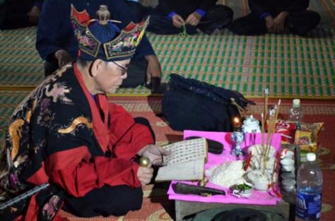 Một thầy Tào đang khấn lễ bằng chữ Nôm Tày.