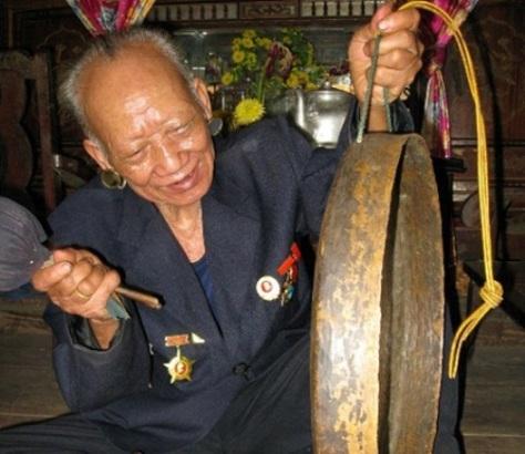 Già làng Kê Xâr, tộc Tà Ôi,  đánh chiếc chiêng đồng.