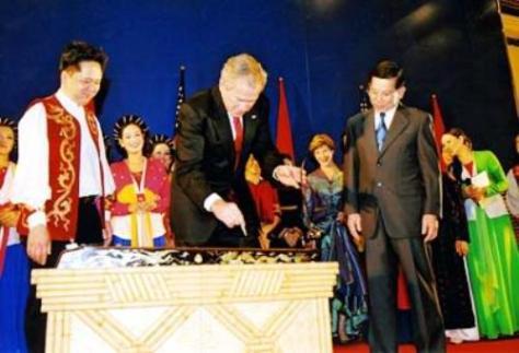 Cựu Tổng thống Bush gẩy đàn bầu trong dịp APEC Hà Nội 2006.