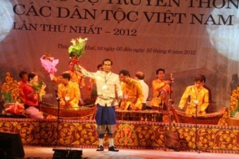Nghệ sĩ Lý Hùng - quyền đội trưởng đội thông tin văn nghệ Khmer Bạc Liêu nhận hoa chúc mừng từ ban tổ chức. Sự có mặt của đội đã thổi một luồng không khí tươi mới của miền Nam vào liên hoan.