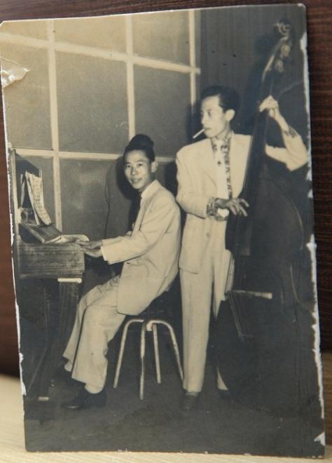Nhạc sĩ Y Vân (đứng) chơi đàn bass cùng với nhạc sĩ Thanh Thoại chơi piano trong ban nhạc năm 1957.