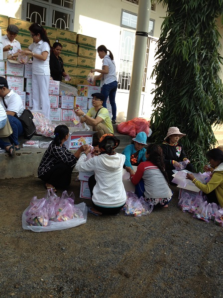 """2/ Ảnh một số mẹ trong giáo xứ cùng với một số người trong đoàn từ thiện """"Trái tim Việt"""" Tp. HCMphân chia quà ra thành từng phần."""