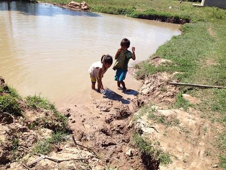 2/ Ảnh hai em chuẩn bị đào một rãnh bùn.
