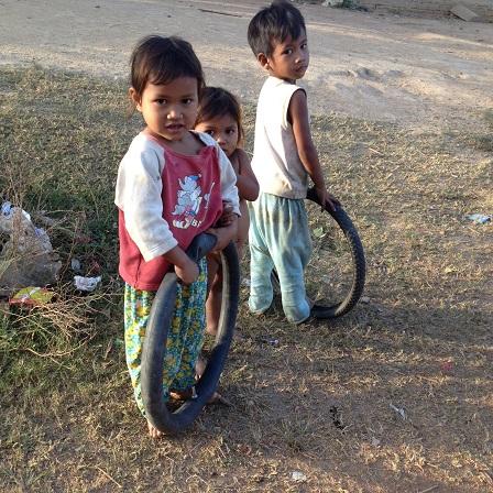 1/ Ảnh ba người con nhỏ của bố mẹ Trim buổi chiều trên con đường của Buôn Làng