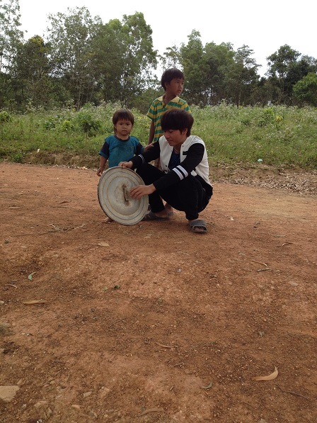 Ảnh ba người con của bố mẹ Thiếu lấy nắp xoong gõ làm tiếng cồng chiêng để chơi.