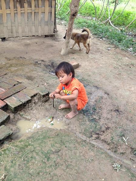 1/ Anh em Thao bên xóm đào ngồi cột dây cao su vào đầu cây que để thả xuống khuấy vũng nước sìnhlên chơi.