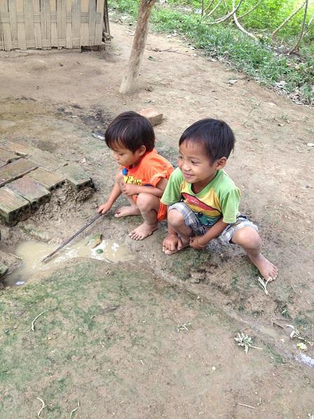 2/ Anh em Thao đã cột xong dây vào cây que và vui vẻ khuấy vũng nước bùn lên chơi với em Win.