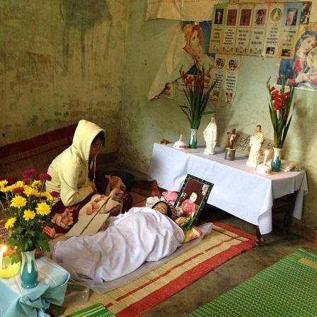 1/ Ảnh mẹ em Phúc ngồi bên em Phúc trước khi em Phúc được tẩm liệm.