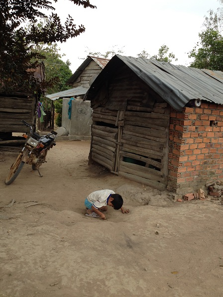 Ảnh em Số chơi một mình trong sân đất bột bên hông nhà.