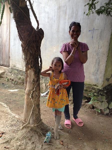 Ảnh mẹ Xi và người con gái út đứng dưới gốc cây trước nhà bên xóm Đào, vui vì Yăh đến thăm.