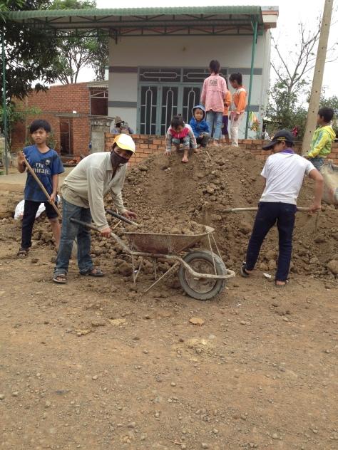 Ảnh những người con của bố mẹ Joang ở thôn Năm, Chúa nhật được nghỉ học giúp bố mẹ Joang chuyển đất đắp nền xây nhà.