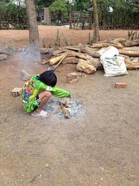 1/ Ảnh em Biển buổi sáng trời lạnh bên bếp lửa trước sân nhà ở thôn Hai trong Buôn Làng.