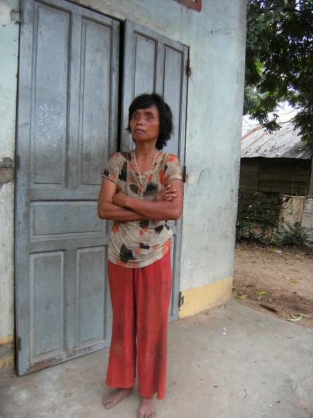 Ảnh cô Lúa bị mù đứng trước cửa nhà của cô ở thôn Hai, căn nhà được xã xây theo chương trình 134.