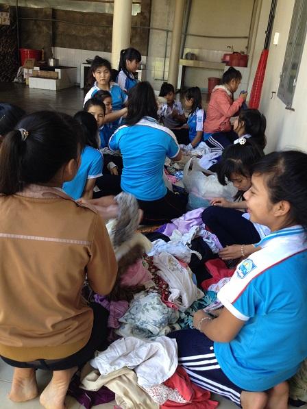 1/ Ảnh các em học sinh Lưu trú phấn khởi lựa áo quần Sida Yăh mua về cho những người trong gia đình.