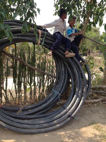 2/ Ảnh hai em Hoal và Xiêm đã trèo lên trên cuộn dây tưới cà-phê và đang ngồi chơi như cưỡi voi.