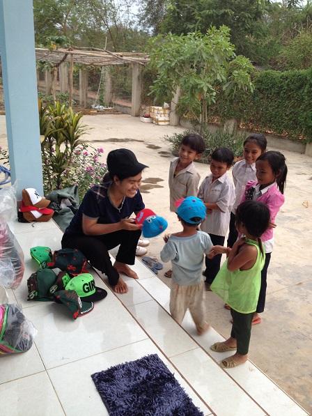 1/ Trong sân nhà các Yăh, Yăh phát mũ cho các em nhỏ trong Buôn Làng.