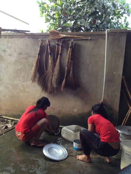 Ảnh em Mỹ Linh (T) và em Mươi (P) đang rửa xoong nhà Lưu trú.