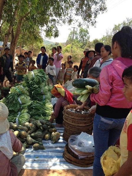 1/ Ảnh các Yăh mang củ quả, rau cá… Đến đặt dưới bóng mát của gốc cây trước nhà bố mẹ Thiếu, đểchia sẻ cho các gia đình bên xóm Đào.