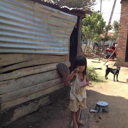 2/ Em Hảo đứng ăn sáng bên hông nhà ở thôn Năm.