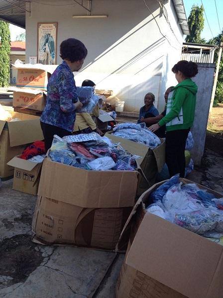2/ Trước cổng sau của giáo xứ Buôn Hằng, các mẹ thuộc giáo họ Chí Hòa Tp. HCM đang phânchia áo quần mới, để chia sẻ với anh em Buôn Hằng mùa hè 2016.
