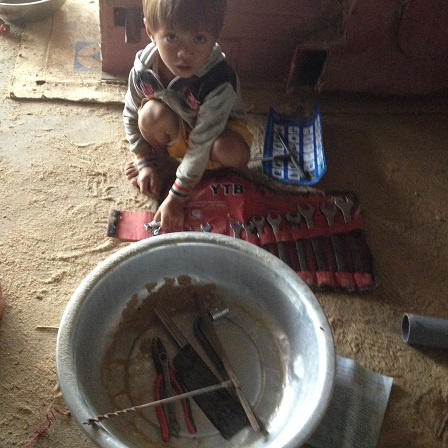 Em Anh con bố mẹ Thân ngồi chơi dưới đất bột với những dụng cụ sửa máy của bố.