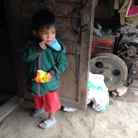 Ảnh em Xiêm hai tuổi đứng ăn Osin trước của nhà hàng xóm là nhà của bố mẹ E ở thôn Năm.