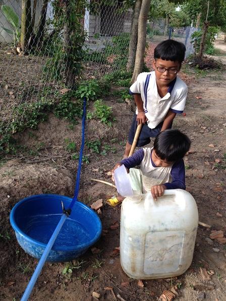 Em Xây và em Số tận dụng múc từng giọt nước chảy từ ống dây bị thủng đem về dùng.