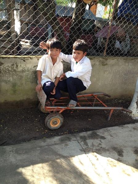 Ảnh em Kali và em Số ngồi trên xe đẩy thư giãn sau giờ học giáo lý.