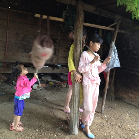 Ảnh em Y đang quay chiếc balô đi học của chị Sun được treo móc trên cây trong chái nhà.