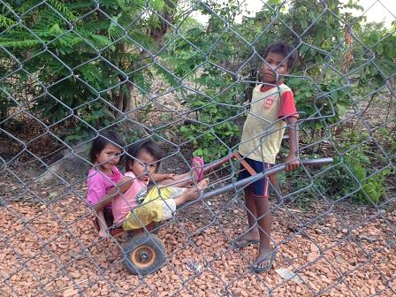 Ảnh ba em nhỏ chơi xe trước hàng rào nhà Yăh