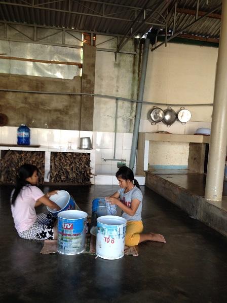 Em Hiểu và em Sal đang sơn các thùng đựng nước trong các phòng tắm nhà Lưu trú.