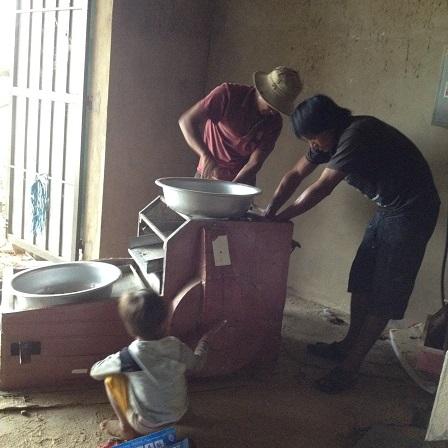 Ảnh bố Gươm và bố Thân bên thôn Hai sửa máy xay lúa của gia đình.