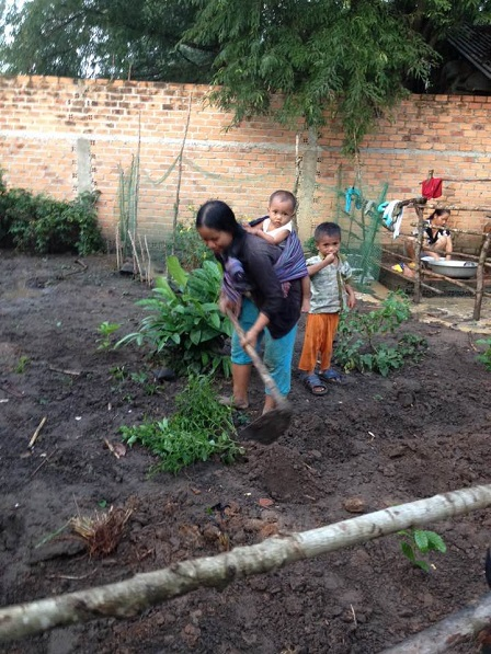 1/ Sau cơn mưa mẹ E địu con tranh thủ ra cuốc vườn.