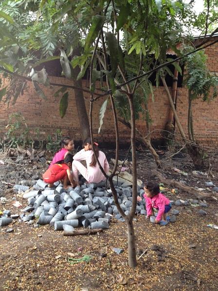 Ảnh các con của gia đình bố mẹ Nghiệp chơi trên đống đá của giếng khoan.