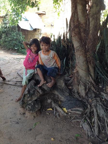 Hai anh em con bố mẹ Sa ngồi chơi dưới gốc cây