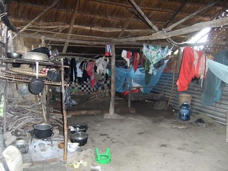 Ảnh phía trong nhà của một gia đình trong Buôn Làng: Vừa nấu bếp, vừa chỗ ngủ và áo quần giăng như bươm bướm.