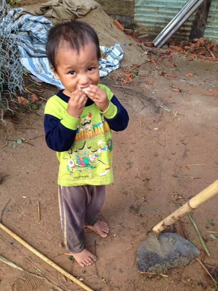 Em Gân đang ăn một khúc nhỏ bắp đỏ nướng trong sân phía sau nhà.