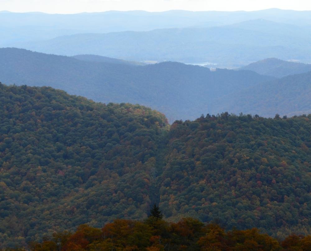 Nhìn gần thì không phải là con đường mà là một khoảng trống vạch thẳng xuyên qua núi. Lại thấy có hồ nước nằm cách đó một dãy núi phía trên.