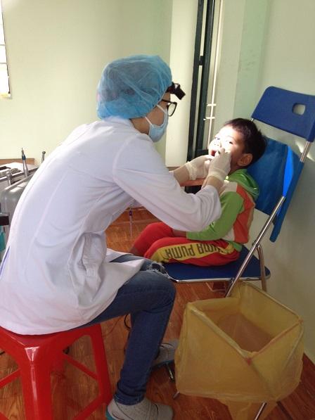 10. Em bé con bố Minh ở Sóc Bù Xiết đang được khám răng