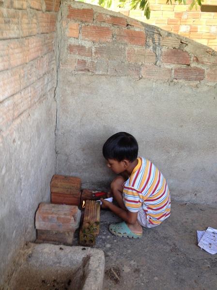 Người con trai út của mẹ Sâm đang một mình chơi đốt lửa trong góc nhà.
