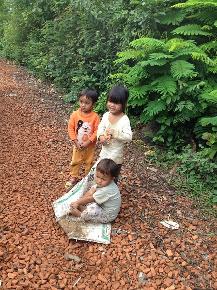 Ảnh ba em nhỏ con bố mẹ Likam lấy bao chơi kéo xe trên con đường bên hông nhà Yah