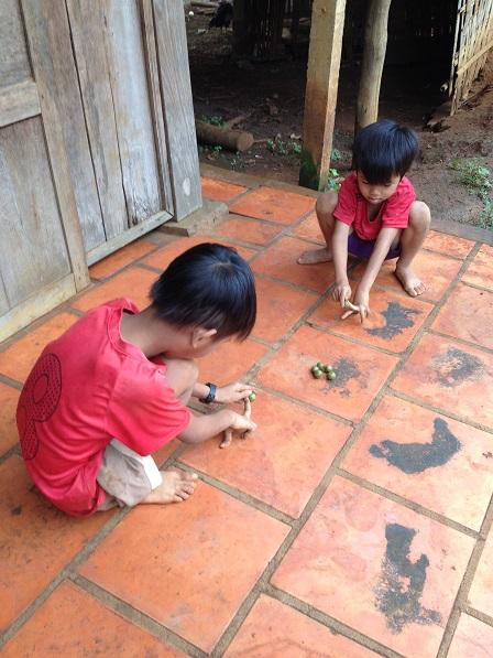 1/ Hai em nhỏ ở sóc Bù Xa chơi bắn bi.