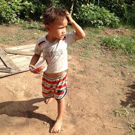 Em Khel vừa ăn cơm vừa đi ra vườn chơi.